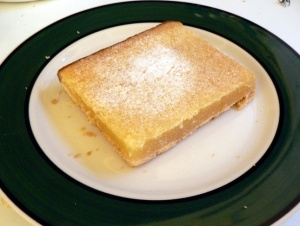 lemon bar on plate with dusting of sugar